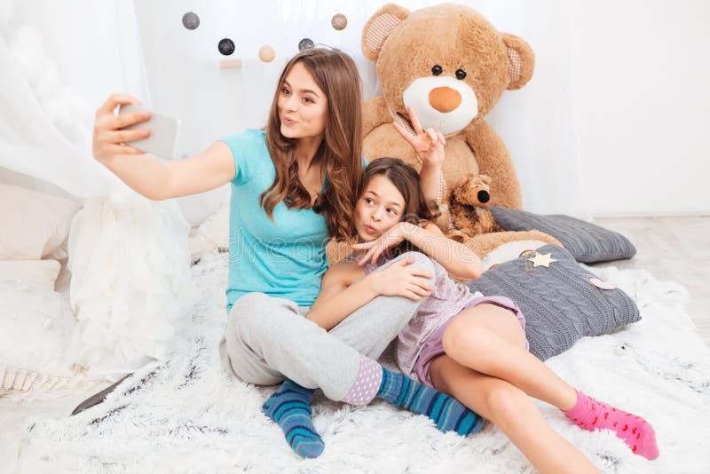 Due sorelle felici incantanti che fanno i fronti dell'anatra e che prendono selfie immagini stock libere da diritti
