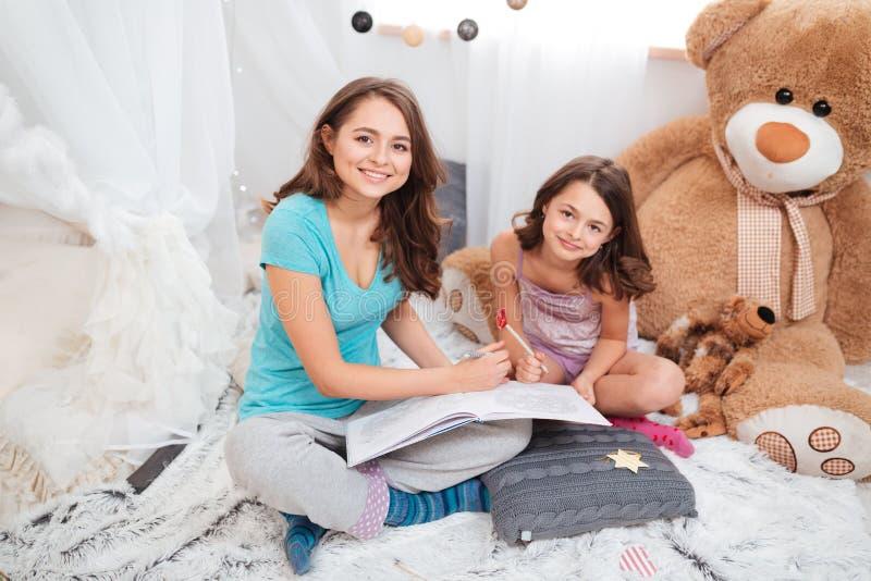 Due sorelle sorridenti sveglie che si siedono e che riuniscono fotografia stock libera da diritti