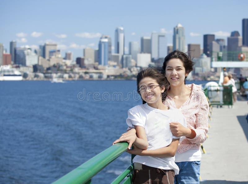 Due sorelle sulla piattaforma del traghetto, orizzonte di Seattle fotografia stock libera da diritti