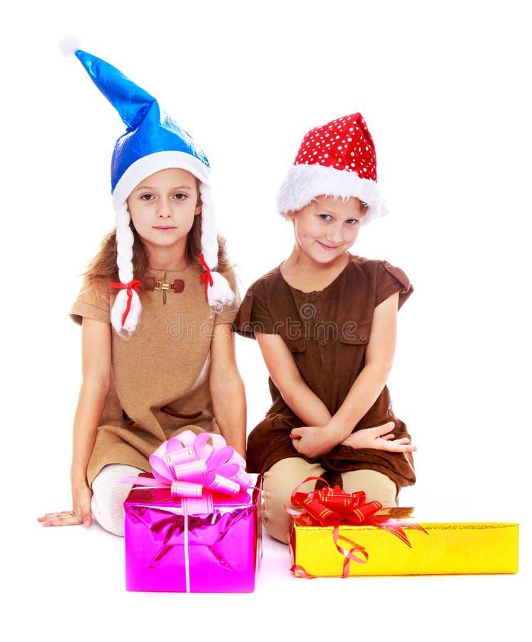 Due sorelle sveglie in cappelli di Natale stanno considerando immagine stock libera da diritti