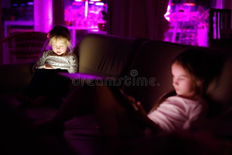 Due sorelline adorabili che giocano con una compressa digitale in una stanza scura immagini stock libere da diritti