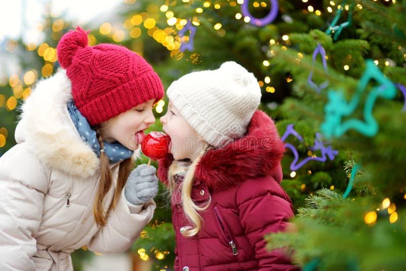 Due sorelline adorabili che mangiano le mele rosse coperte di glassa dello zucchero sul mercato tradizionale di Natale fotografia stock libera da diritti