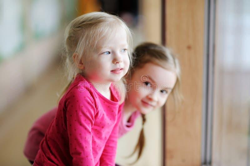 Due sorelline adorabili dalla finestra fotografia stock libera da diritti