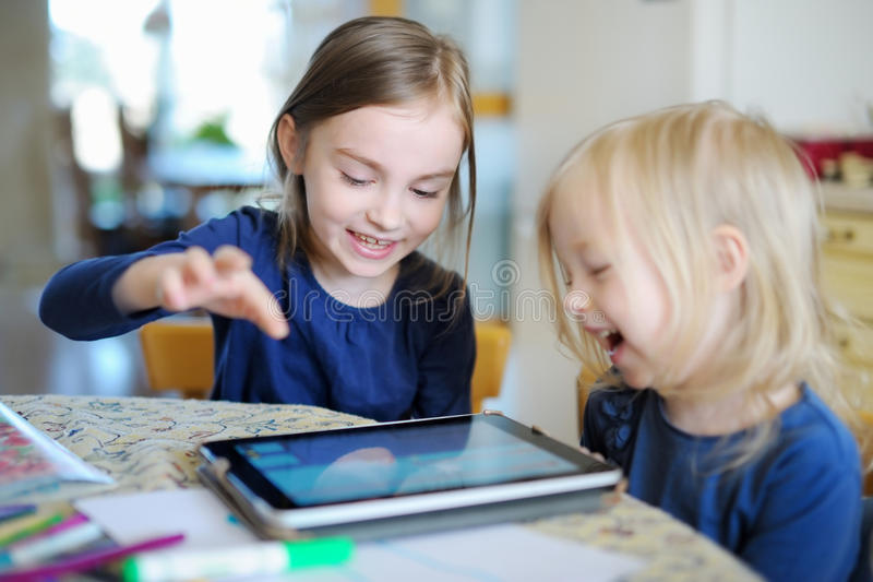 Due sorelline che giocano con una compressa digitale immagine stock libera da diritti