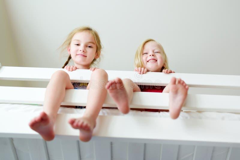 Due sorelline che imbrogliano intorno, giocanti e divertentesi nel letto di cuccetta gemellato immagini stock