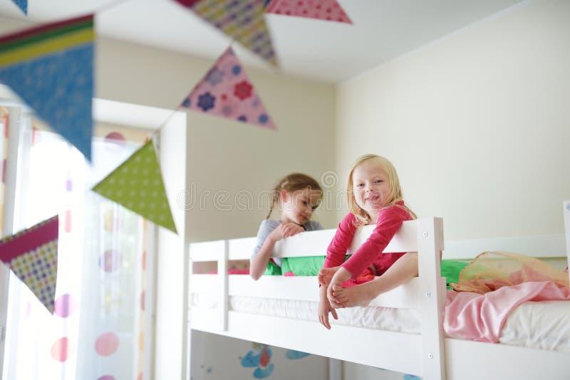 Due sorelline che imbrogliano intorno, giocanti e divertentesi nel letto di cuccetta gemellato fotografia stock