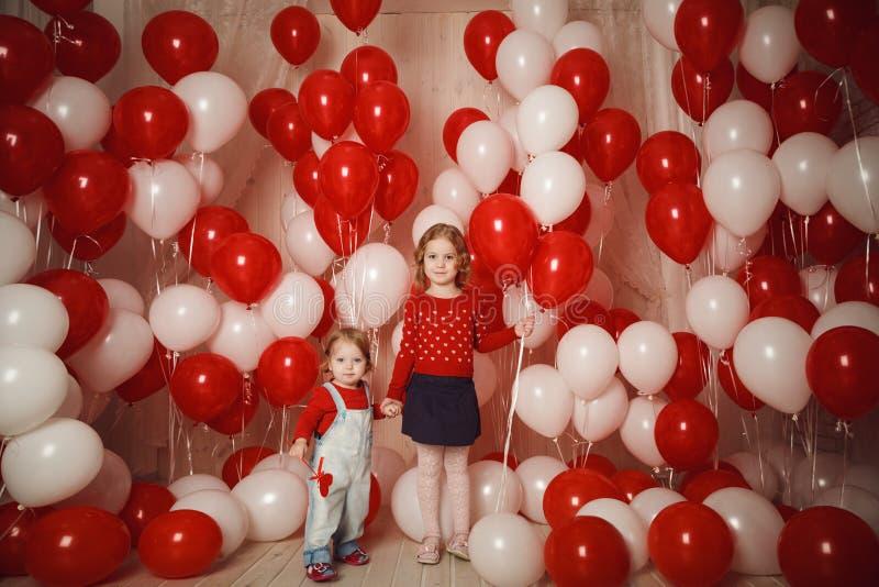 Due sorelline con i palloni rossi e bianchi fotografia stock
