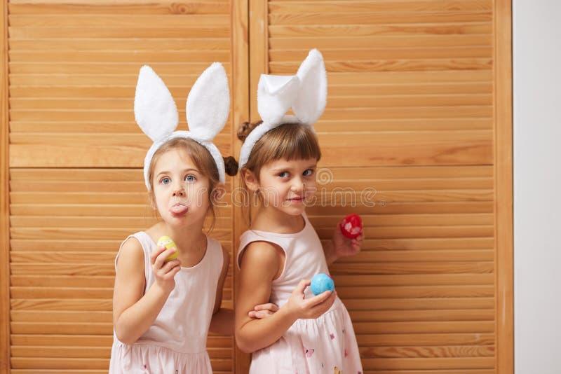 Due sorelline divertenti nei vestiti con le orecchie del coniglio bianche sulle loro teste si divertono con le uova tinte in loro immagine stock libera da diritti