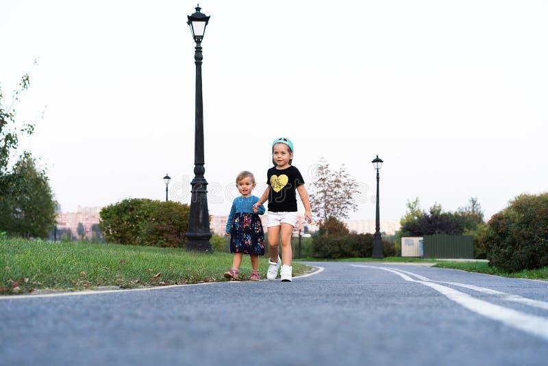 Due sorelline funzionano sulla strada in parco un giorno di estate soleggiato Bambine sveglie fotografia stock libera da diritti