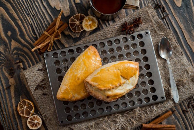 Due spezie sparse panini dei chiodi di garofano del limone della cannella Rivesta di ferro la tazza di tè su un fondo scuro di le fotografie stock
