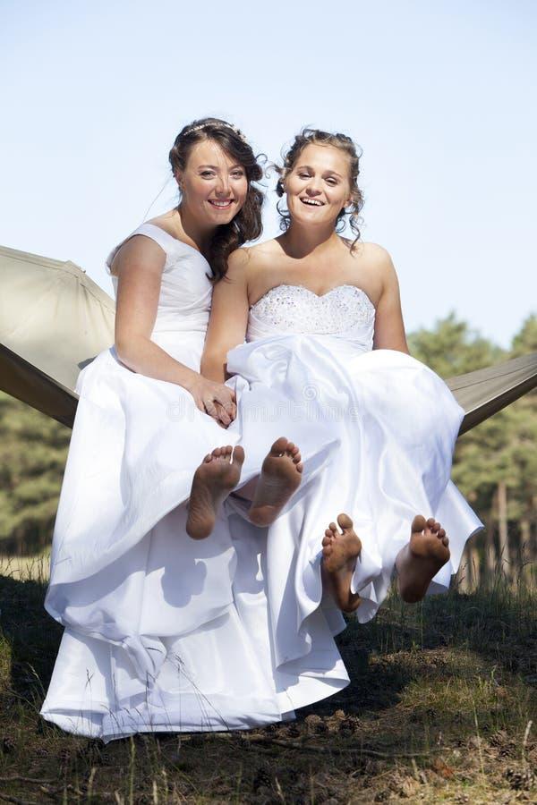 Due spose in amaca contro cielo blu con il fondo della foresta fotografie stock