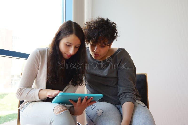 Due studentesse che esaminano il pc della compressa immagini stock libere da diritti