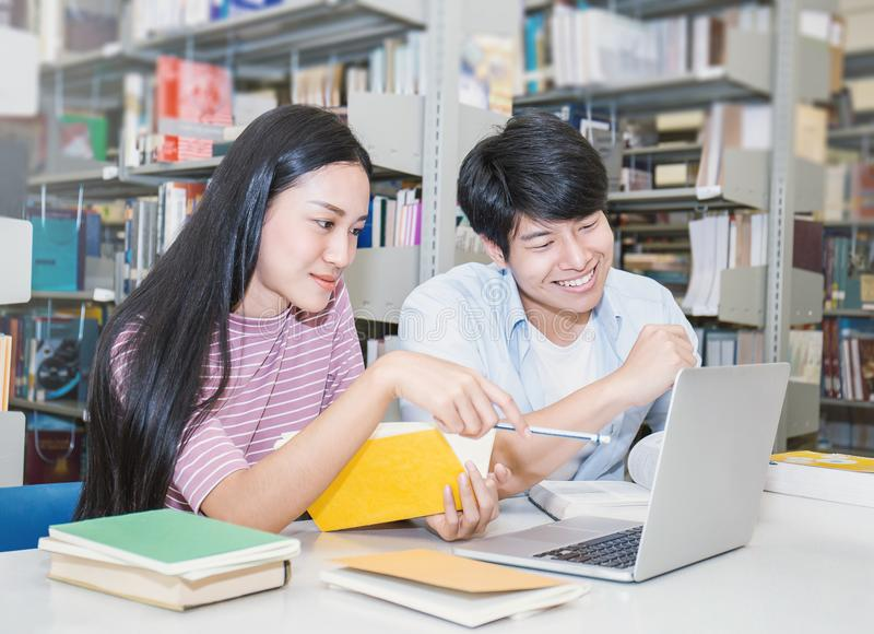 Due studenti di college asiatici che utilizzano computer portatile nella biblioteca fotografia stock libera da diritti