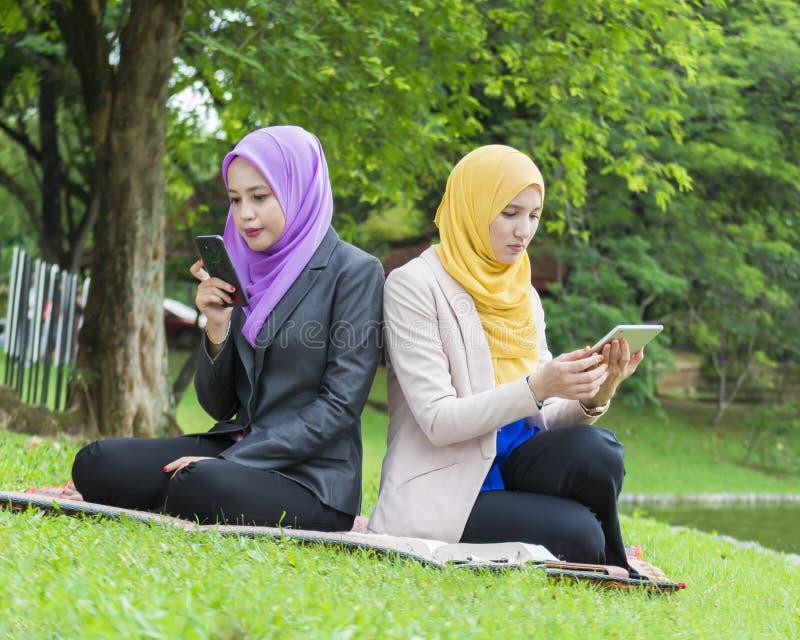 Due studenti di college che prendono foto nel parco fotografia stock libera da diritti