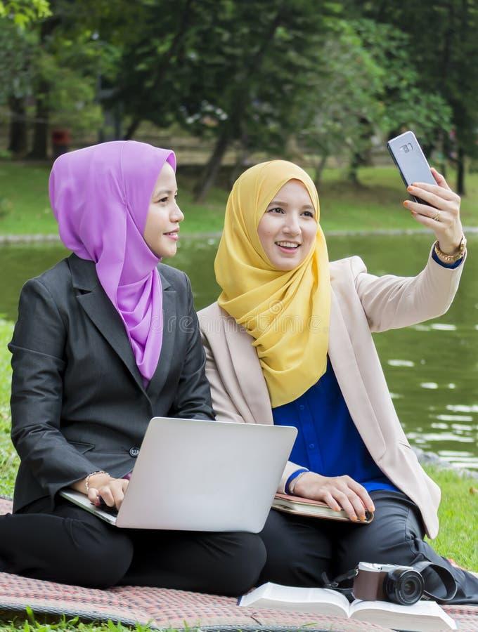 Due studenti di college che prendono foto nel parco fotografie stock libere da diritti