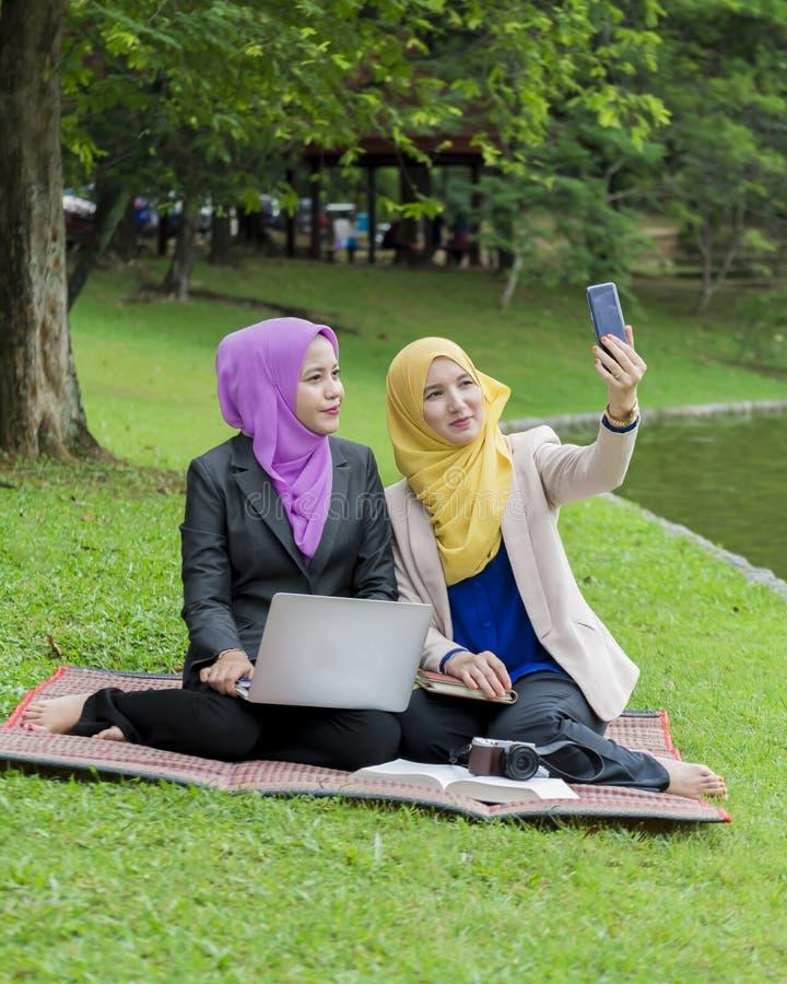 Due studenti di college che prendono foto nel parco fotografia stock