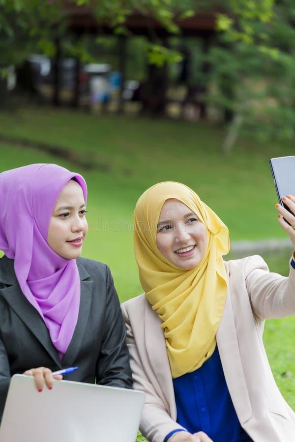 Due studenti di college che prendono foto nel parco immagine stock