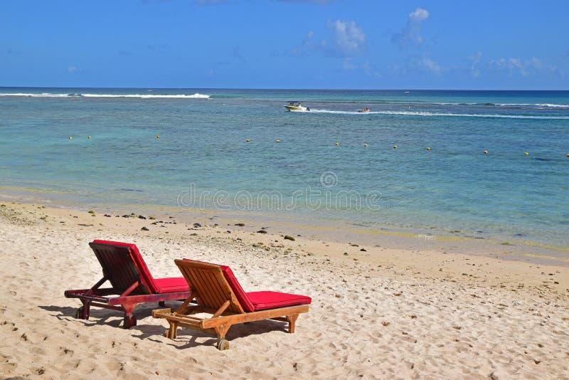 Due sundecks con i cuscini rossi sulla spiaggia sabbiosa che affronta mare blu azzurrato pulito con la barca di velocità nel fond immagine stock
