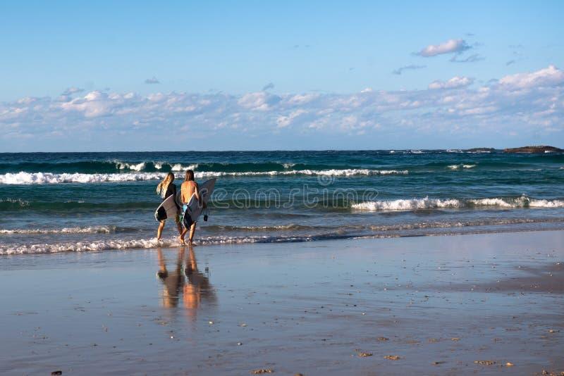 Due surfisti che camminano su una spiaggia australiana immagini stock
