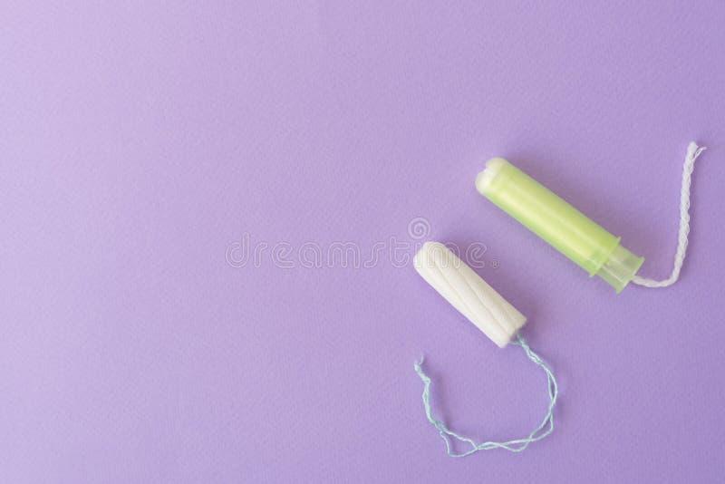 Due tamponi del cotone con l'applicatore verde chiaro e senza applicatore su un fondo viola Tipi igienici di tamponi immagini stock