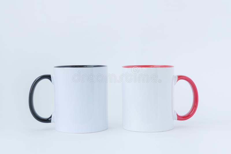 Due tazze bianche, con una maniglia nera e rossa fotografia stock