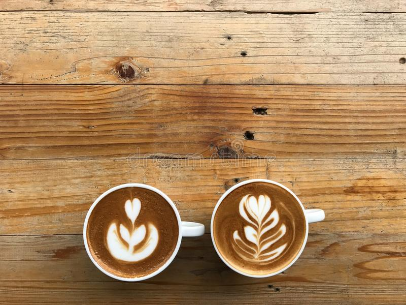 Due tazze del caffè caldo del latte con arte differente del latte due, hanno messo sopra la tavola di legno marrone naturale fotografia stock libera da diritti
