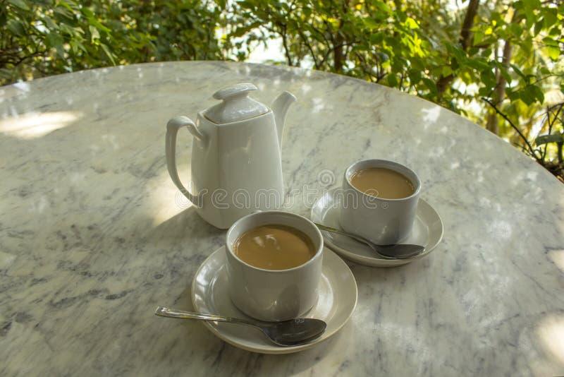 Due tazze della bevanda a base di latte su un piatto con i cucchiai vicino ad una teiera ceramica bianca su una tavola di marmo s fotografia stock
