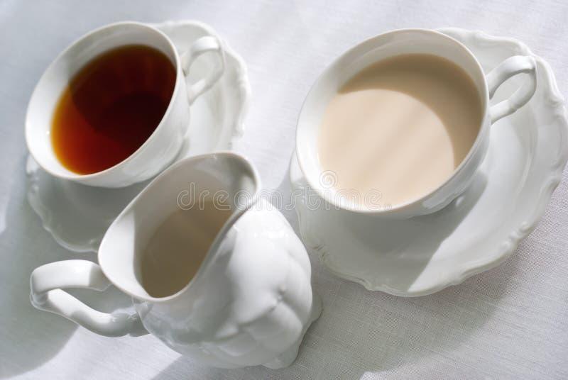 Due tazze della brocca di latte e del tè. fotografie stock libere da diritti