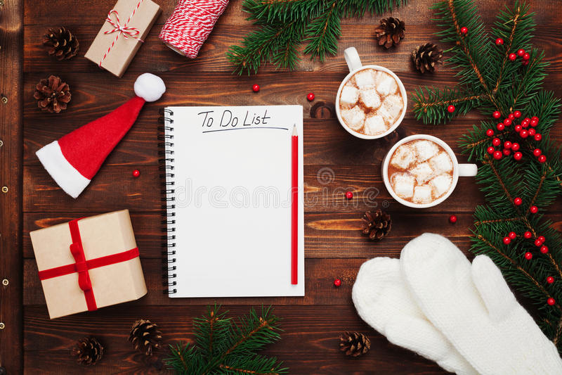 Due tazze di cacao o di cioccolato caldo con la caramella gommosa e molle, i regali, i guanti, l'albero di abete di natale ed il  immagine stock