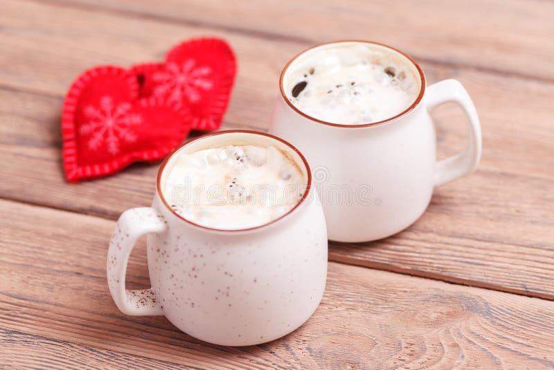 Due tazze di caffè con cuore ritenuto decorativo sul primo piano di legno del fondo Il concetto del San Valentino, Natale immagini stock libere da diritti