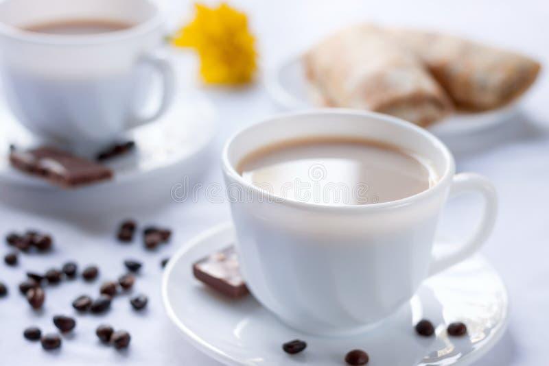 Due tazze di caffè con latte, pancake con il cioccolato al latte e dell'inceppamento Prima colazione di mattina per due fotografie stock libere da diritti