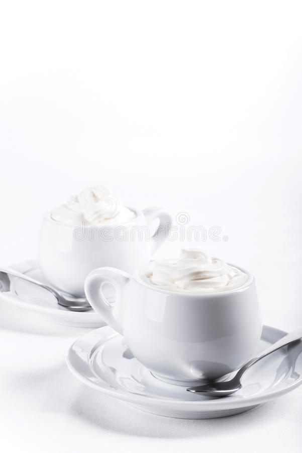 Due tazze di caffè con panna montata molto bianca immagine stock
