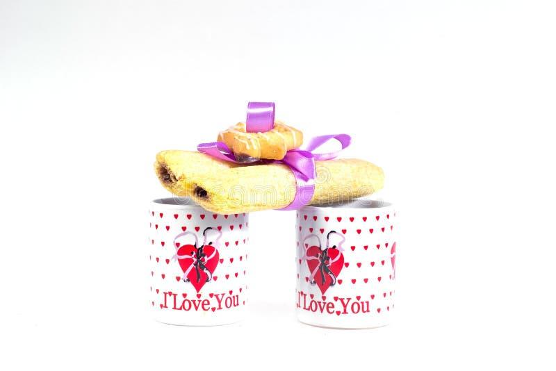 Due tazze di caffè con una dichiarazione di amore e dei biscotti legati con il nastro su un fondo bianco immagini stock libere da diritti