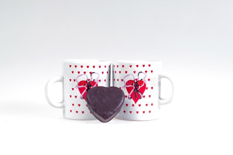 Due tazze di caffè e caramelle sotto forma di cuore su un fondo bianco - faccia colazione per gli amanti fotografia stock libera da diritti