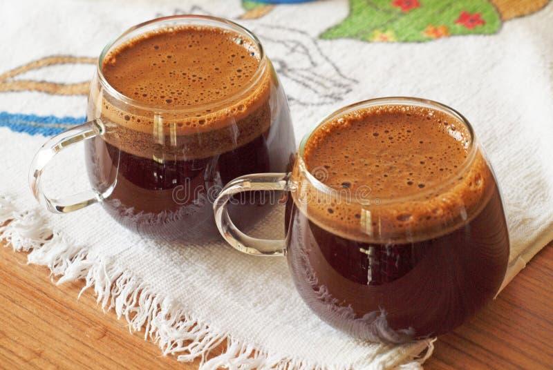 Due tazze di caffè saporito con schiuma, su una tavola di legno ricoperta di materia tessile colorata fotografie stock