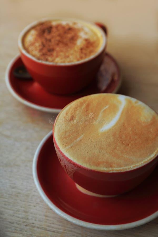 Due tazze di caffè, un latte ed una moca in tazza rossa sulla tavola di legno rustica immagine stock libera da diritti