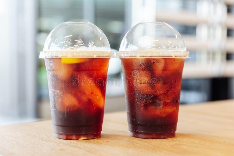 Due tazze di nitro caffè freddo di miscela Iced con il limone sulla tavola di legno con il fondo della sfuocatura immagini stock libere da diritti