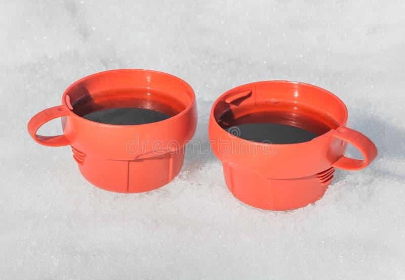 Due tazze di plastica rosse con tè caldo nero con vapore su un esterno bianco del fondo della neve nell'inverno per il picnic fotografie stock libere da diritti