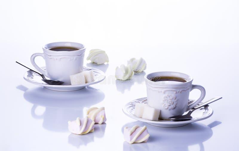 Due tazze di tè con zucchero e le caramelle gommosa e molle fotografie stock