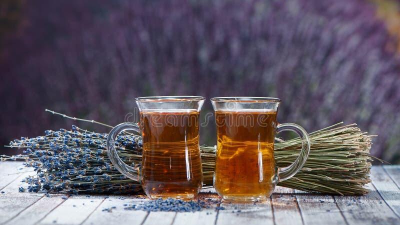 Due tazze di tè e di un mazzo di lavanda su un fondo di una b immagini stock