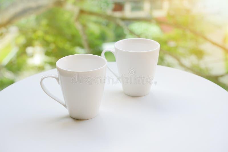 Due tazze, di tè o di caffè sulla tavola sul fondo luminoso del giardino fotografia stock libera da diritti