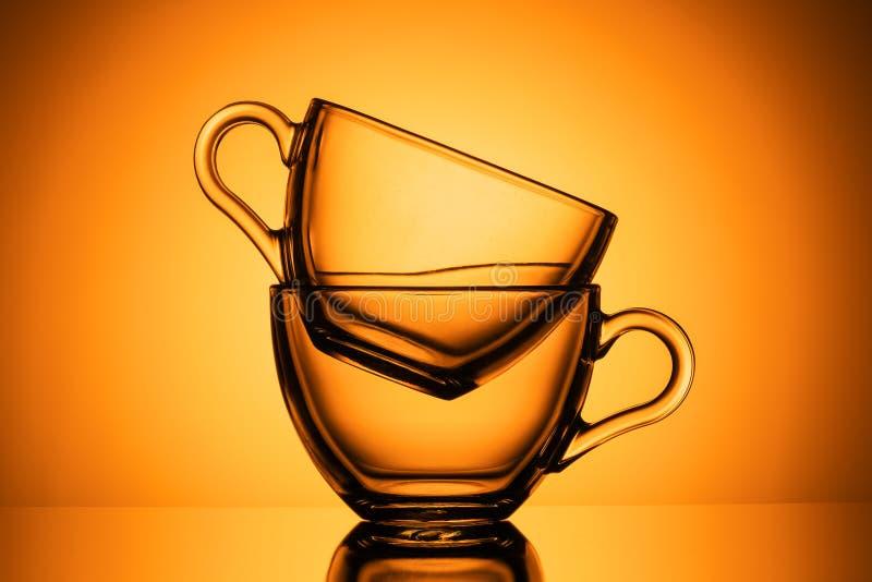 Due tazze di vetro trasparenti per tè Fondo arancio, primo piano, DISPOSIZIONE ORIZZONTALE immagine stock
