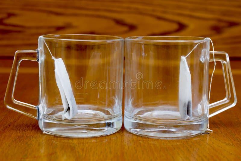 Due tazze e bustine di tè su fondo di legno fotografia stock
