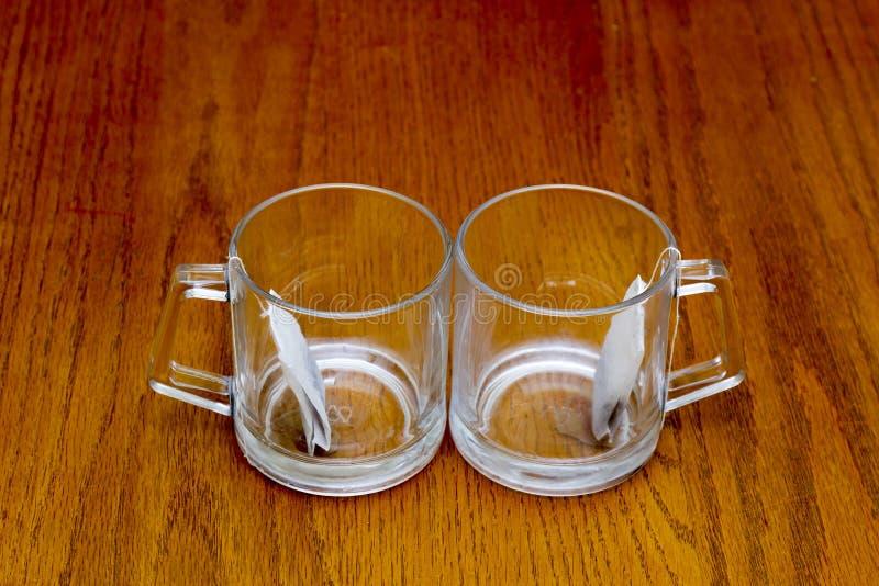 Due tazze trasparenti con le bustine di tè immagini stock