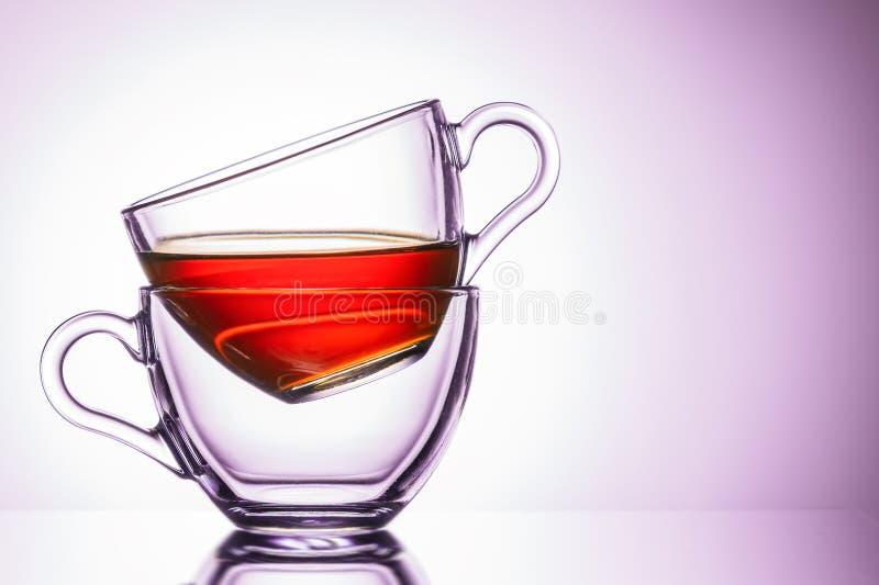 Due tazze trasparenti di tè posizione a sinistra, primo piano Tonalit? rosa immagine stock libera da diritti