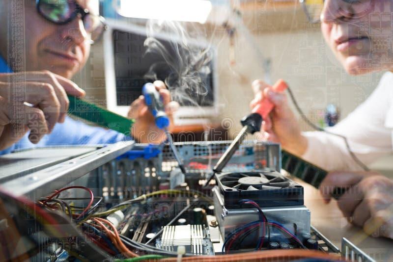 Due tecnici del computer che riparano l'hardware gettano l'immagine della finestra immagine stock libera da diritti