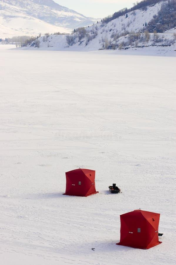 Due tende di pesca del ghiaccio sul lago congelato immagine stock