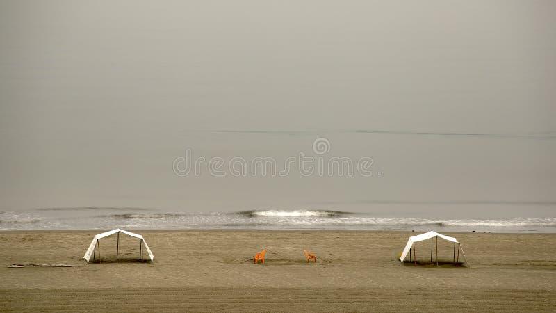 Due tende e due sedie arancio sulla spiaggia immagini stock