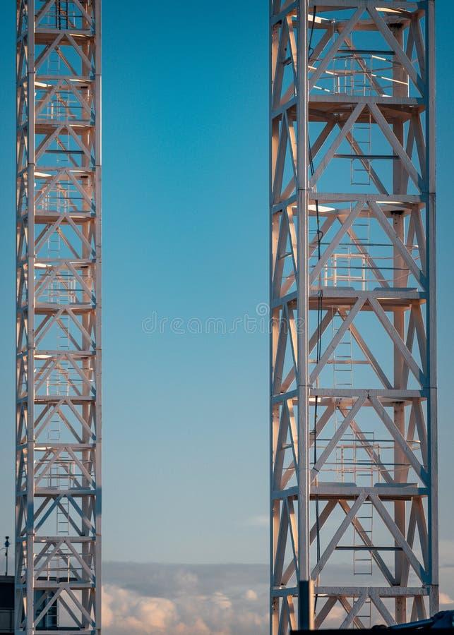 Due torri della gru con il fondo del cielo fotografia stock libera da diritti