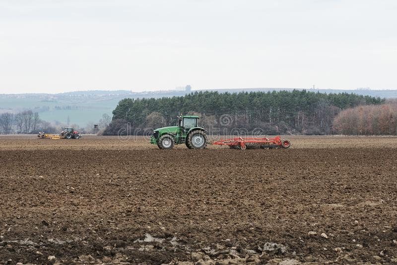 Due trattori che arano un campo ad una foresta sotto un cielo blu - Czec immagini stock